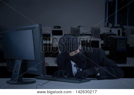 Male robber taking information on the computer while wearing mask in the office at night