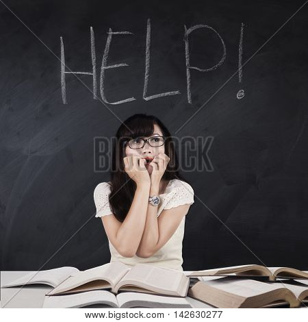 Female high school student studying with book and looks scared with Help word on the chalkboard