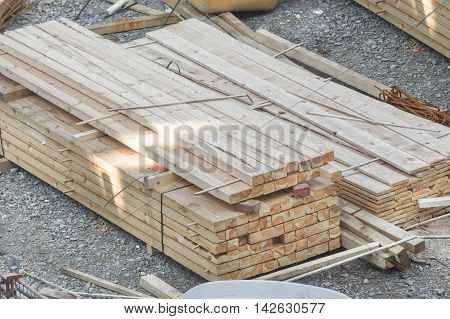 Stacked wooden boards at a construction site.