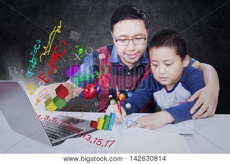 Male teacher teaching his student using laptop with formula of science math and physics in the class