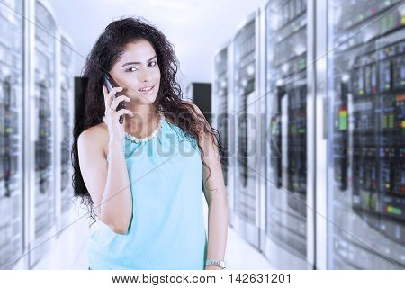 Indian woman talking on the cellphone while standing in the server room