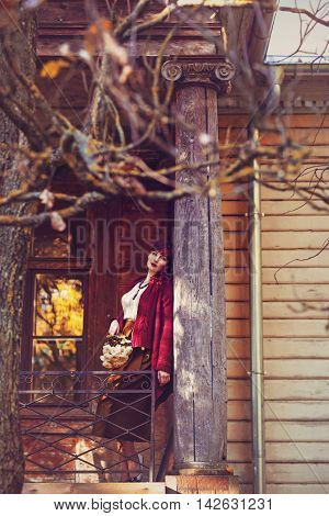 Beautiful young woman in long skirt and wool red scarf standing on old house balcony. Early fall. Outside shot. Ambient light.