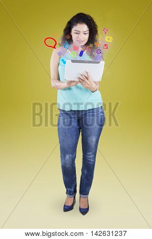 Indian young woman standing in the studio while using a digital tablet with social media icon