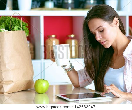 Young woman using a tablet computer to cook in her kitchen .
