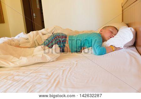 boy sleeps with a bracelet in a hotel in a great beds