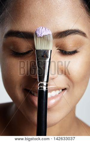 Woman's Portrait With A Brush With A Violeet Cream On It