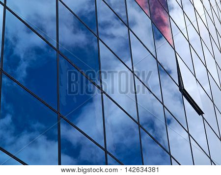 Modern trendy design glass office building with reflection of clouds in the windows