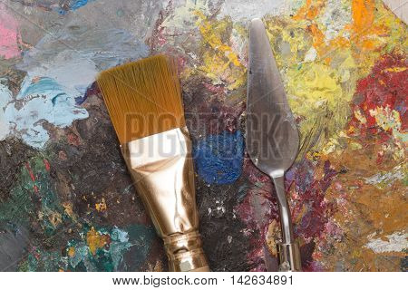 Dirty paint brush and old wooden pallet