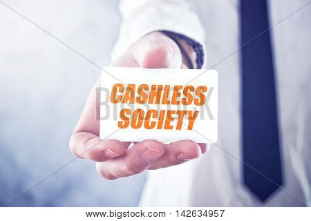 Businessman holding card with Cashless society title concept of promoting mobile and electronic payments without cash money banknotes