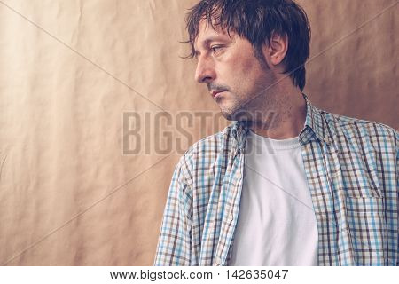 Depressive sad man profile portrait male person with unhappy gloomy facial expression leaning on to wall and looking to a side.