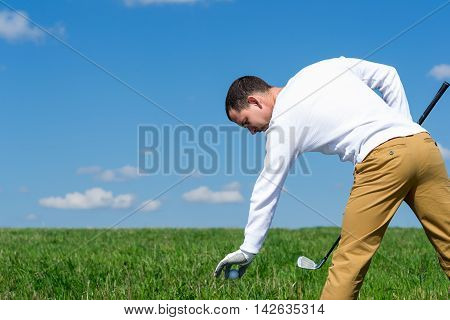 player leans to put the golf ball