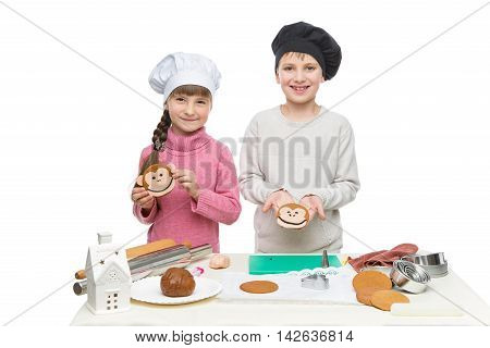 Beautiful boy and girl in chef hats making christmas cookies. Children standing behind table isolated over white background.