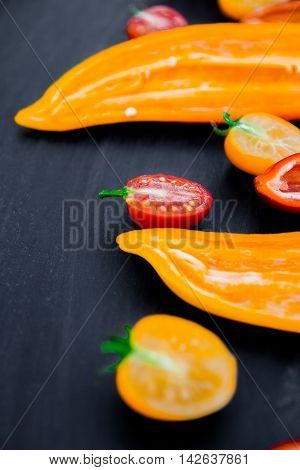 Mixed Of Half Red And Yellow Pepper With A Green Branch Near Cherry Tomato On  Black Backround. Clos