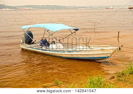 sailing motor boat on dirty water brown color with green grass