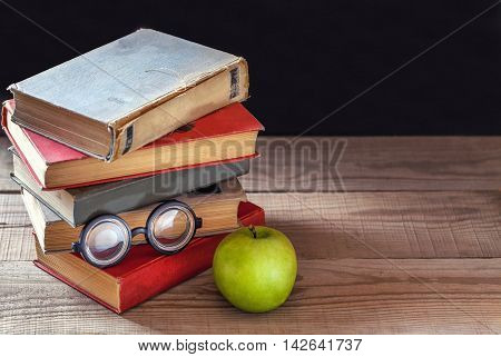 A stack of old vintage books green apple and round glasses on a rustic wooden table on black school board background
