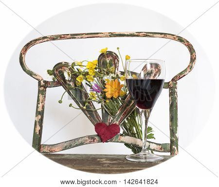 glass of red wine over the old iron chair with yellow wildflowers and a heart in the middle, white background,with photo cropping