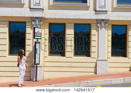 MONACO, MONACO - JULY 17, 2015: Unidentified woman waits for a bus at the bus stop in Monaco, Monaco.