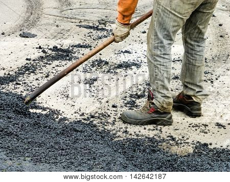 Worker close potholes with asphalt in summer