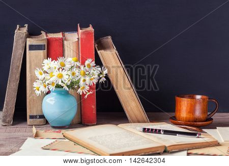 The open old book lying on the wooden table among vintage envelopes vase with daisies and a cup with a hot drink. Rustic still life.