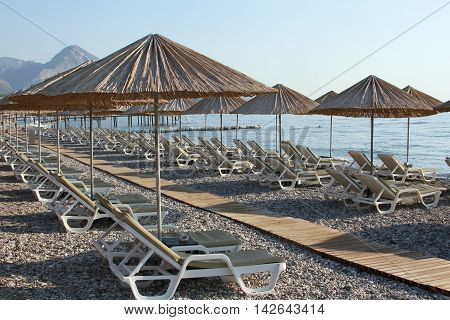 Rocky Beach with sun beds and umbrellas
