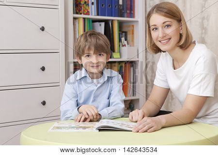 beautiful young caucasian teacher with elementary school student sitting at the green table with the textbook. Looking at the camera and smile. Horizontal color image close-up