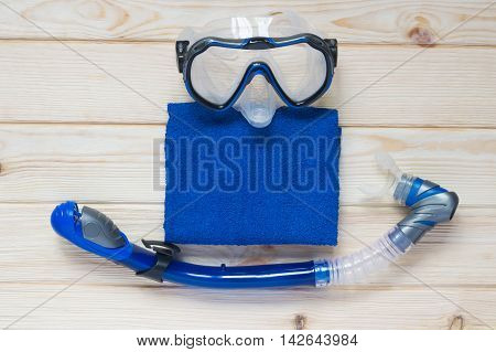 Equipment for swimming with a towel, on a wooden table