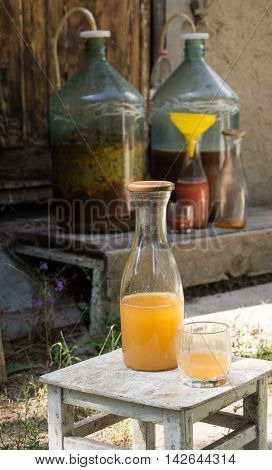 Production of domestic fruity wine. Home-made wine in a bottle and glass on the background of large tanks with wine