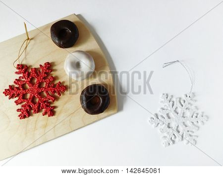 Donuts on a cutting board on a white background surrounded by christmas decorations