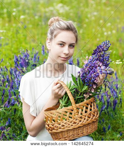 beautiful girl with basket of lupine flowers in hands