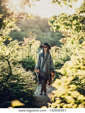 Boho style young woman in hat and poncho walking in summer park at sunny day