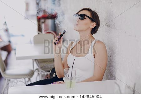 spectacular young brunette enjoys fashion and healthy electronic cigarette