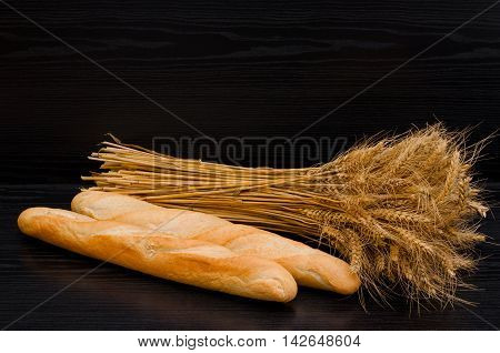 Two white loaf and a sheaf on a black background