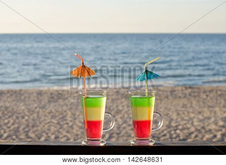 Tricolor cocktail on the bar counter with a sandy beach overlooking the sea relax