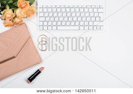 Feminine office desk workspace mockup with flowers, handbag, beige lipstick, keyboard and notepad on white background.