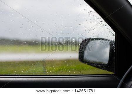 Raindrops splashed on a side window of a car viewed from the inside