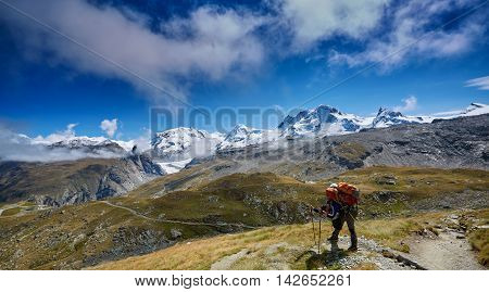 tired hiker with backpack on the trail in the Apls mountains. Trek near Matterhorn mount