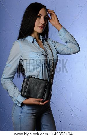 Beautiful stylish brunette in jeans holding a black clutch. fashion concept.