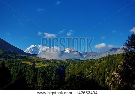 Snow capped mountains under deep blue sky.