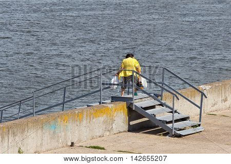 An elderly woman is on the bridge (the bridge) through a concrete (brick) block. She carries heavy shopping bags from the store. In the background is the water (river or lake).