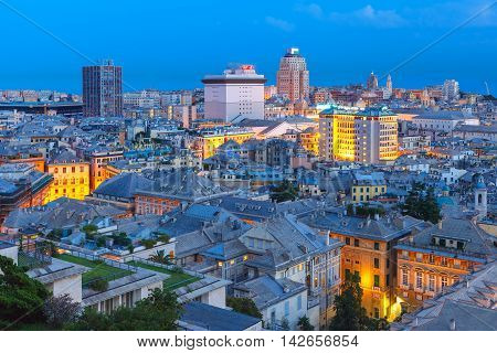 Aerial view of old town and port with cranes and ship at night, Genoa, Italy.