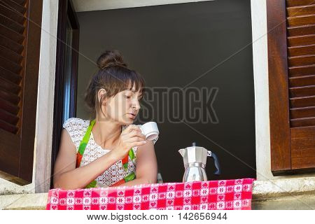 Portrait of concentrated woman is looking at hot coffee cup in her hand sitting near open window with traditional European wood brown shutters