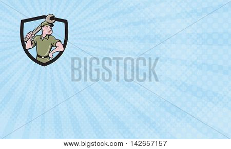 Business card showing Illustration of a mechanic wielding holding spanner wrench looking to the side with one hand on hips viewed from front set inside shield crest on isolated background done in cartoon style.