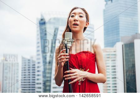 Asian Woman Singing With Mic On The Rooftop Of The Building In Urban Scene