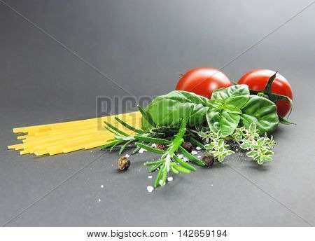 Ingredients for cooking with spaghetti pasta and fresh herbs.
