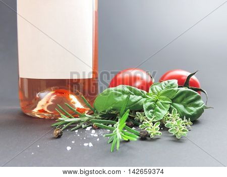 Ingredients for cooking and red wine bottle on gray background.