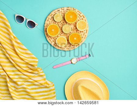 Fashion. Summer Beach set. Tropical Fruit Citrus, Orange, Lime. Bright Summer Color. Stylish woman Sunglasses, Trendy hat. Essentials creative art. Minimal concept. Top view. Yellow blue background