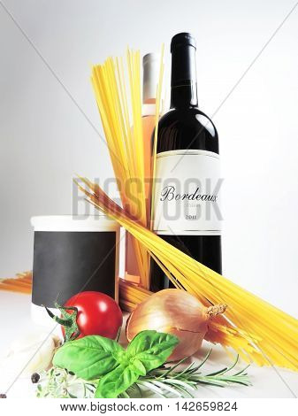 Ingredients for cooking and red wine bottle on white background.