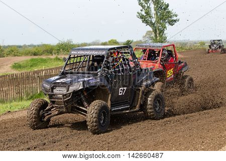 ARNCOTT, UK - MAY 4: Two unnamed drivers competing in the UK SXS RZR series hit a left hand turn at speed causing mud to fly into the spectators area on May 4, 2014 in Arncott