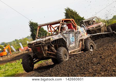 ARNCOTT, UK - MAY 4: An unnamed driver competing in the UK SXS RZR series hits a left hand turn at speed causing mud to fly from the burm on May 4, 2014 in Arncott
