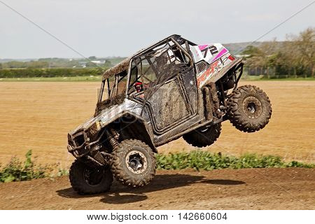 ARNCOTT, UK - MAY 4: An unnamed driver competing in the UK SXS RZR series lands awkwardly on the front offside wheel having just jumped the table-top on May 4, 2014 in Arncott